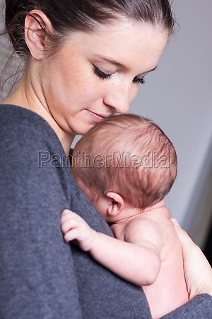 szczesliwa mloda matka trzymajac noworodka od